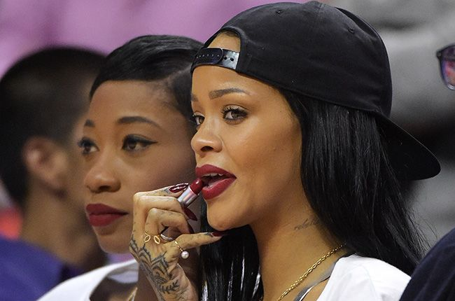 Sitting courtside with best friend Melissa Forde, Rihanna reapplies her own Riri Woo MAC COsmetics lipstick in the second half of Los Angeles Clippers play the Oklahoma City Thunder playoff game on May 9, 2014.