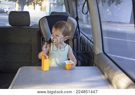 Cute little boy sitting father van and eating yogurt and orange juice. Resting on the way concept