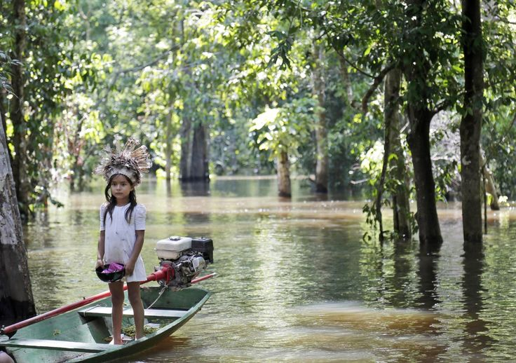 A young girl waits for visitors on a small boat on the Amazon River during the 2014 soccer World Cup near Manaus, Brazil, on Monday June 23, 2014. Manaus is one of the host cities for the World Cup. (AP Photo/Marcio Jose Sanchez)