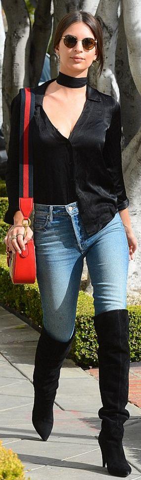Who made Emily Ratajkowski's black thigh boots, skinny blue jeans, red print handbag, sunglasses, and black satin shirt?