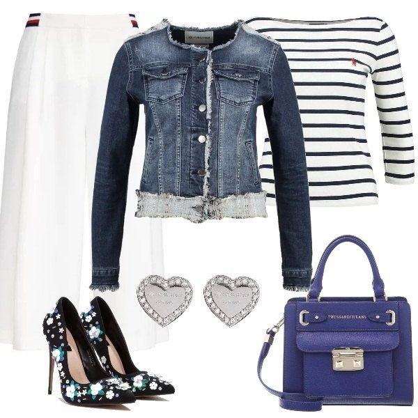 Tacchi alti anche per un look casual, composto da pantaloni bianchi a vita alta, maglietta a manica lunga a righe bianche e blu, giacca di jeans con scollo tondo. Borsa a mano blu e décolleté con tacco alto a fantasia floreale.