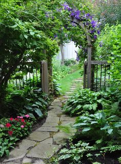 I think all gardens should have some sort of pathway. This is beautiful! Flagstone walkway and arbor.