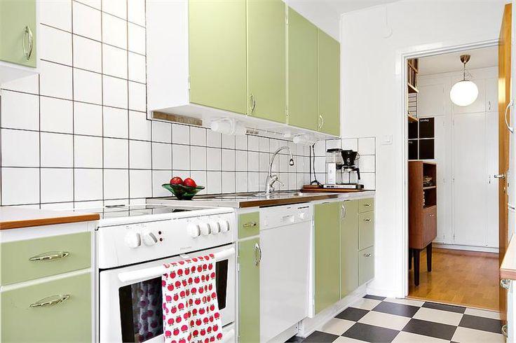 Snygga lampor under överskåpen. Pannlappskrokar under överskåpen. Rutigt golv. Snygga gröna skåpluckor.