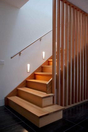 Full height wooden bannister offers screening from, but also a view of the stairs