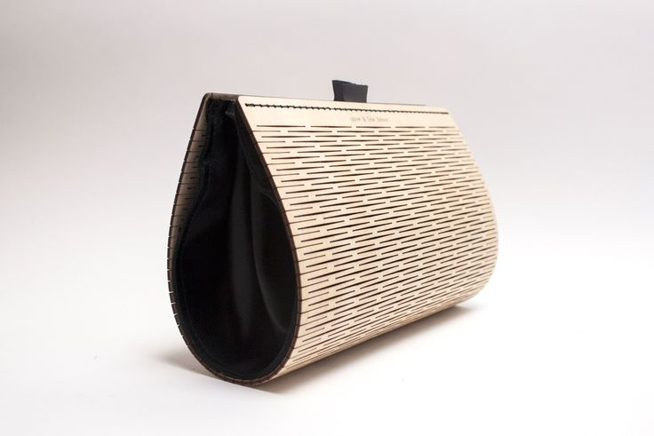 A flexible wooden bag with a linear pattern made by laser cutting the wooden exterior. The bag is paired with a leather interior to contain your goods.