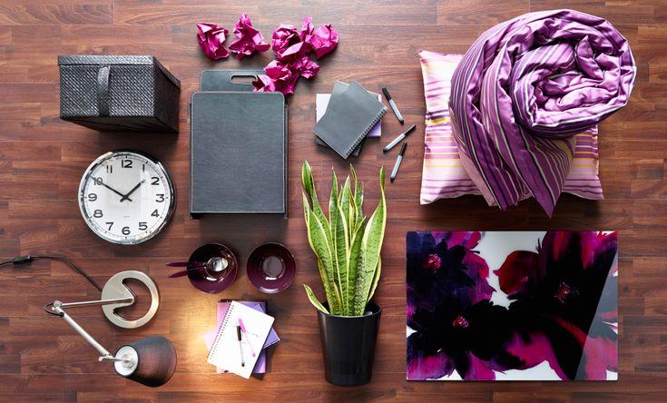 Imagem de uma caixa de cartão preta, um relógio de parede, um cesto de papéis, um conjunto de capa para edredão e fronhas em roxo, um candeeiro de secretária, um quadro com flores roxas, da IKEA.