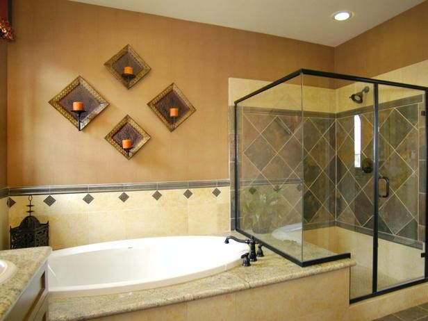 Warm Bathroom Tones: This master bathroom offers sufficient dimensions for its shower and tub combination. Warm tones found in the tiles and countertops define this space. From HGTVRemodels.com