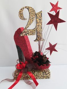 For this 21st birthday centerpiece we used our high heeled shoe painted and glittered red with a black heel. A number 21 was created with the leopard print and the base. Red stars added extra zing.…
