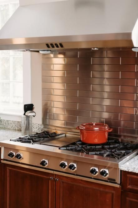 A sleek stainless steel subway tile backsplash is a nice complement to the stainless steel cooktop in this transitional kitchen.