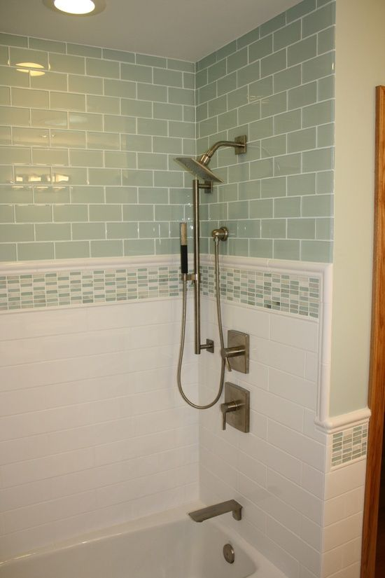 renovated bathroom tiled with pale green subway tiles on top. with white  tile on bottom.