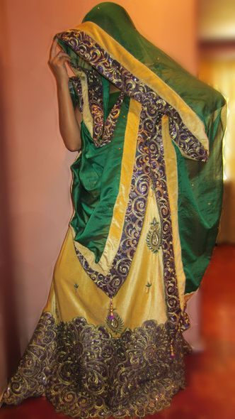 Maize gold lehenga designed using a purple sequinned applique and zardozi green paisley motifs teamed up with a green organdy dupatta and blouse. A perfect wedding / occasional outfit to flaunt this season !!