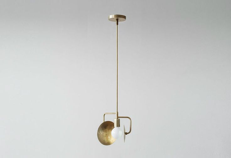 Orbit pendant light designed by Workstead. 	The Orbit pendant lamp features a single or double spun brass disc, which orbits like a planet around the single glowing bulb. It can be arranged in a variety different orientations, depending upon the changing light throughout the day. Dimmable. Spun brass disc, brass tubing and canopy. 	Dimensions: 	Small - 18w x 18d x 61cmh 	Medium - 18w x 18d x 91cmh 	Large - 18w x 18d x 122cmh  	Bulb: 	E26 Base 25-60W Bulb, G25 Globe (required)