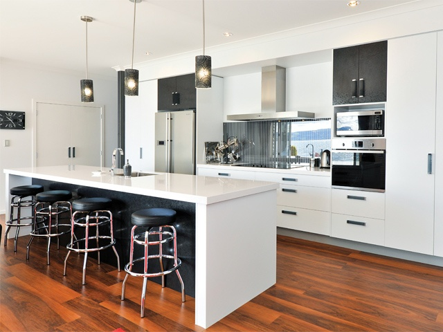 The modern, open plan kitchen with stainless steel and chic black accents is perfect for hosting.