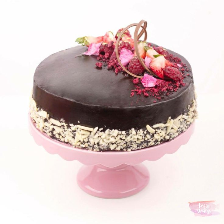 Moist and fluffy chocolate cake with chocolate buttercream, almond ring, topped with fresh berries , edible petals and chocolate curls