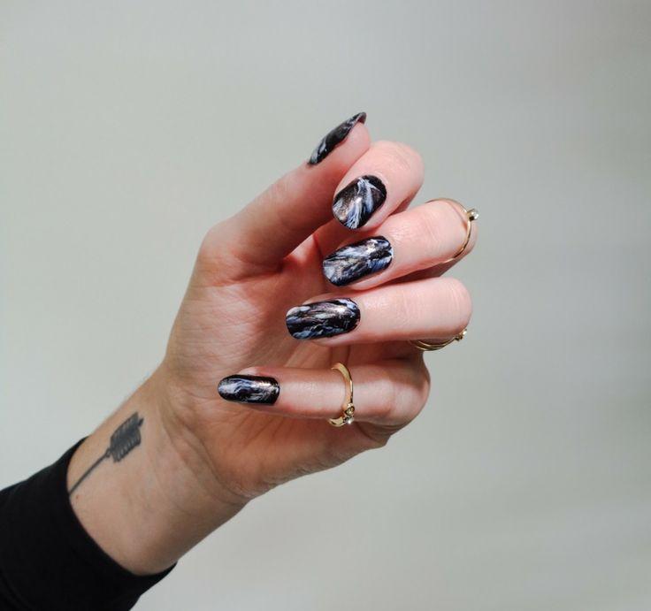Unghie gel nere, effetto marmo riflessi blu, mano di una donna con tatuaggio polso