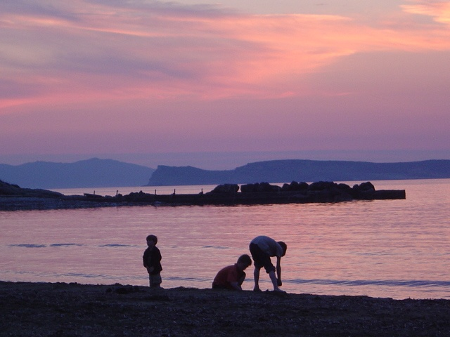Kids playing by the sea shore on Agios Stefanos Beach in Corfu.