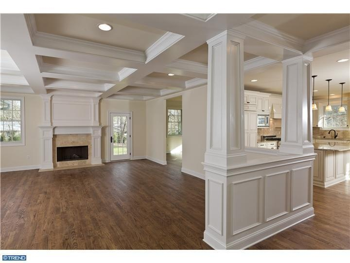 coffered ceiling...open floor concept...crown molding...wainscotting...hardwood floors...white kitchen