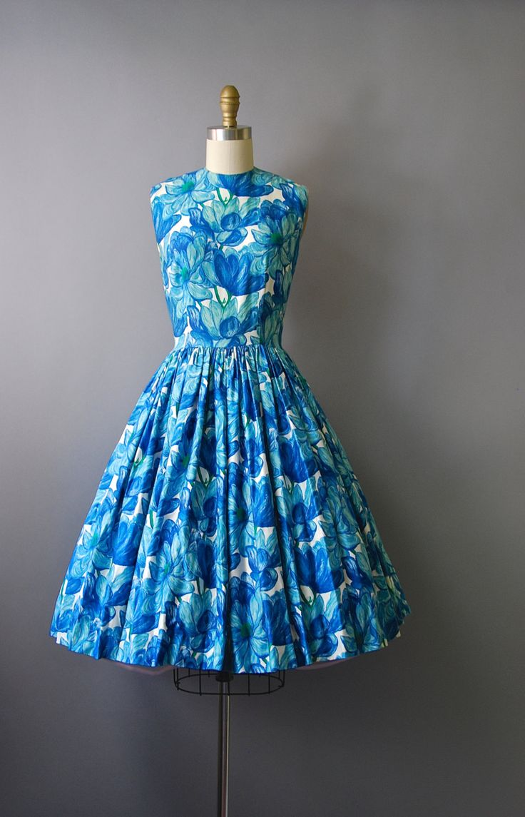 Lovely 1960s blue floral sleeveless dress with nipped waist, very full circle skirt, bright blue floral print, and hidden back zipper. Unlined.
