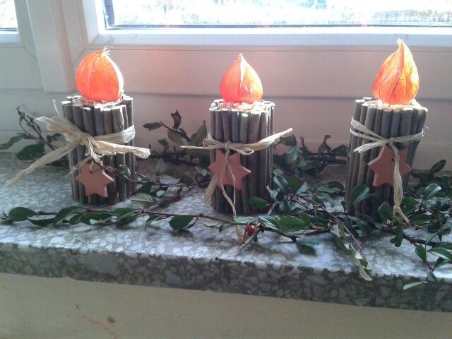 Kerze mit Holzstäbchen auf Klopapierrolle und Lampionblume als Flamme