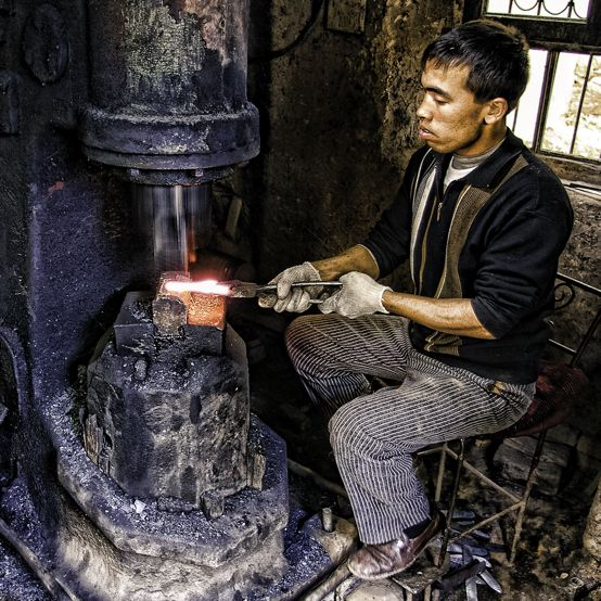 A craftsman shapes the blade on a Uyghur knife inside a small foundry in a village outside Kashgar.