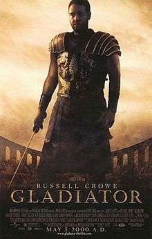 A man standing at the center of the image is wearing armor and is holding a sword in his right hand. In the background is the top of the Colosseum with a barely visible crowd standing in it. The poster includes the film's title, cast credits and release date.