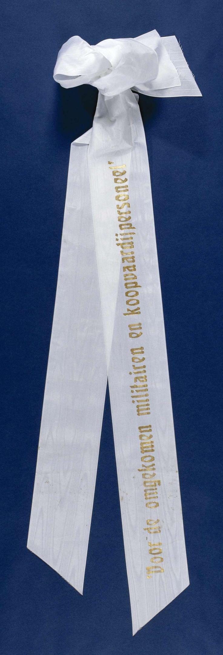 Anonymous | Lint 'Voor de omgekomen militairen en koopvaardijpersoneel', Anonymous, 2000 | Twee aan elkaar gebonden witte linten, gelegd op 4 mei 2000 bij het Nationaal Monument op de Dam. Het bovenste lint is v.z.v. een gouden opdruk. Onderste lint is blanco. Linten zijn aan de uiteinden schuin afgeknipt. Aan een zijde tot strik samengebonden met ijzerdraad. IJzerdraad gebogen t.b.v. bevestiging aan krans.