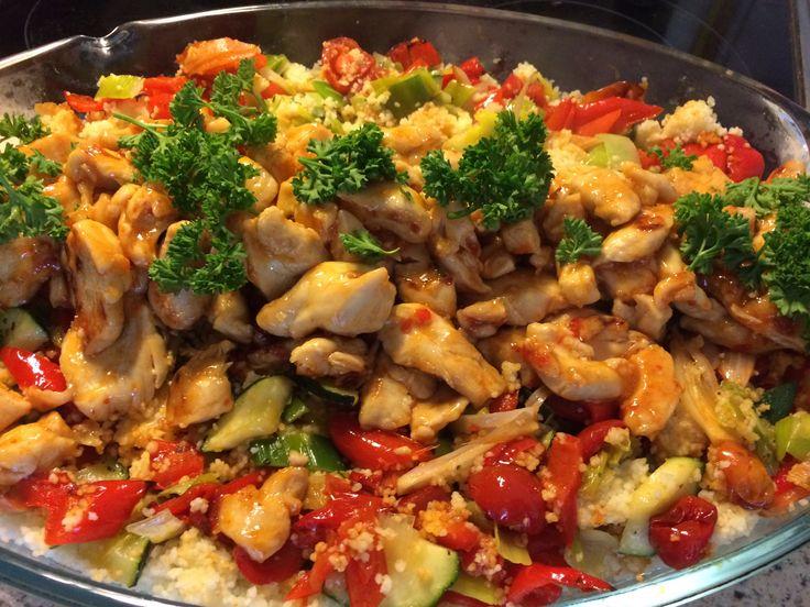 Couscous met geroosterde paprika, sjalotten en tomaten uit de oven, en gebakken courgette en prei. Bovenop: kip gebakken in chilisaus.