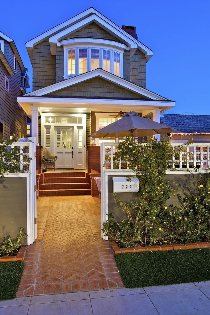 love love love, the door, bow front  window on second story, and transom windows around door, cedar shake porch roof, and shape of house above porch. As well as the transom topper to the front yard fence.