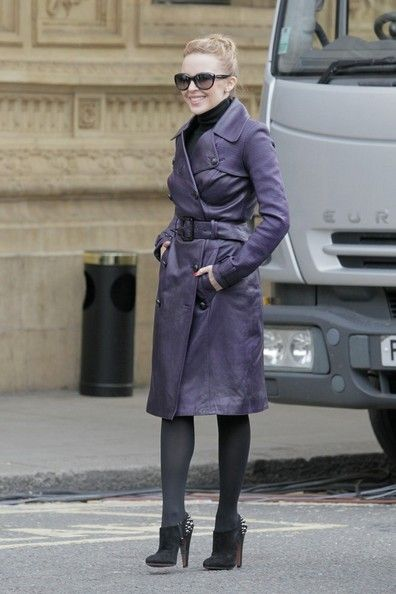Kylie wearing fierce studded boots along with a purple coat.