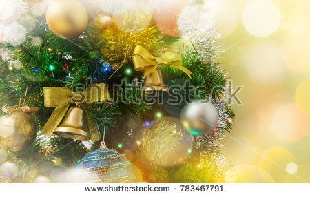 New Year's decorations on Christmas tree on the blurred lights background . Fir branch with baubles and festive lights.