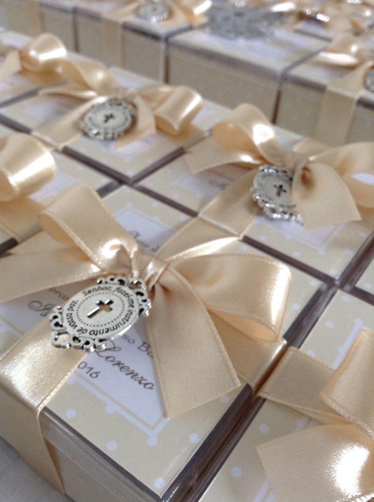 Caixinha de acrílico (7 cm x 7 cm x 4 cm), com garrafinha de água benta e vela de anjinho. A caixinha é forrada com etiqueta adesiva personalizada, cor à escolha do cliente, com oração na tampa, junto com nome e data, amarrada com fita de cetim 15 mm e detalhe de mini terço perolado branco.    PE...
