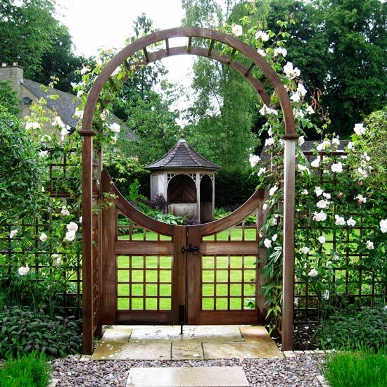 What a pretty scene with a arbour and gateway entrance to the garden .. even a lovely gazebo in the garden