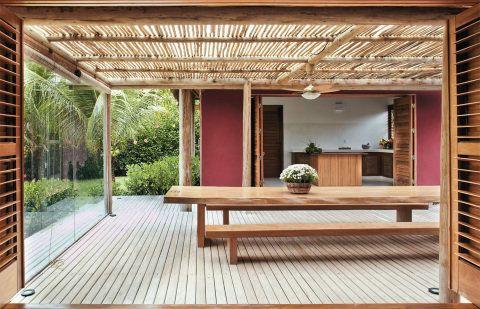 Portas duplas, de cedro com venezianas e palha de tala de dendê (Itapo Arte), ligam o ambiente ao de jantar
