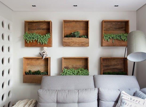 Living | Para trazer o verde para o lar, a solução de Andrea foi instalar atrás do sofá nichos de madeira de demolição, desenvolvidos pela Cali Paisagismo  (Foto: Ricardo Bassetti/Divulgação)