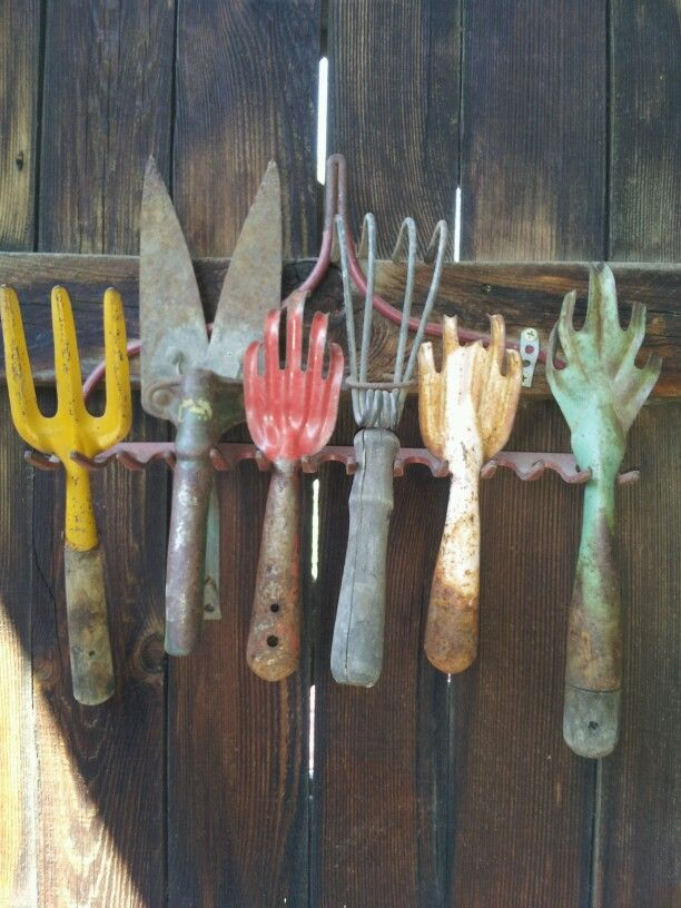 Vintage tools on rake head on fence