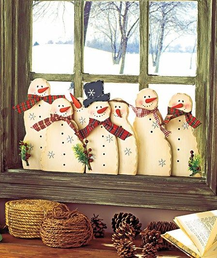 SNOWMAN Family of snowmen on wood sitting on windowsill.