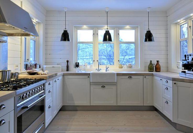 Kjøkkenet domineres av hvite vegger, tak og kjøkkenfronter. Tre svarte taklamper og en stålfarget gassovn skaper et maskulint og sterilt preg.