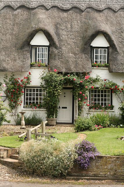 Thatch and roses around the door....