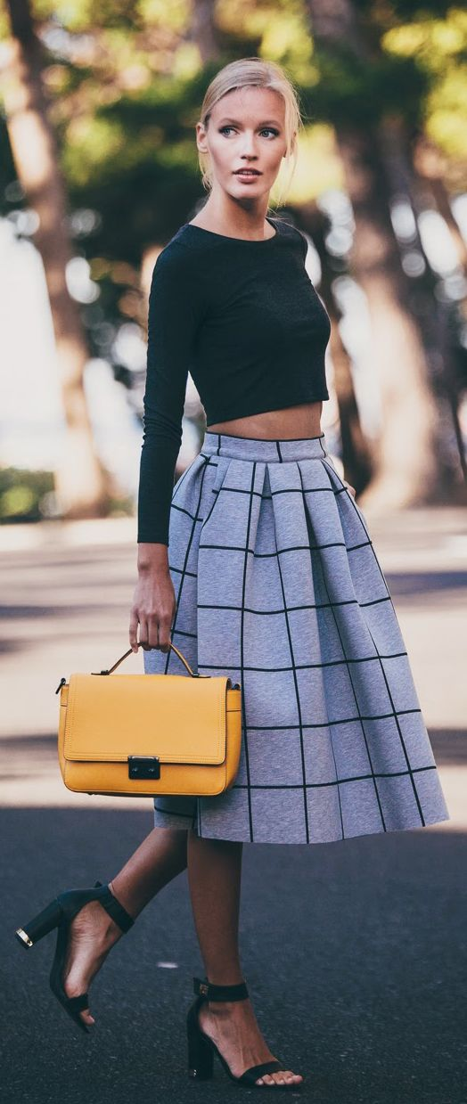 Black crop top, grey and black windowpane midi skirt, black strappy heels, and yellow handbag