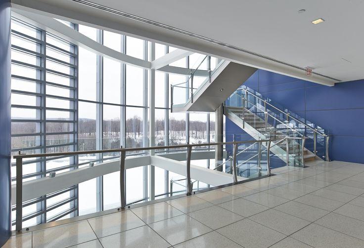 Alla colonna sono collegati i fascioni laterali in acciaio inox e i pianerottoli a sbalzo, e completano l'opera i gradini in pietra chiara, le ringhiere in vetro e il corrimano tubolare. #interbau #stairs #design #customised