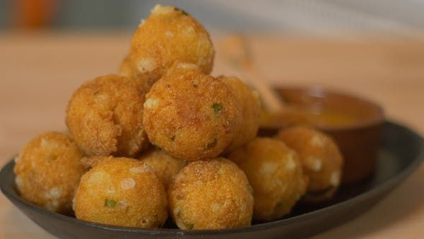 Recipe with video instructions: Hushpuppies are perfect as appetizer, these ones are filled with feta cheese.   Ingredients: 1 cup cornmeal, 1/2 cup all purpose flour, 1/2 cup a finely sliced green onion, 1 teaspoon baking soda, 1/2 teaspoon salt, 3/4 cup buttermilk, 1/2 cup crumbled feta, Vegetable oil for frying, Dipping Sauce: Honey and Yellow Mustard
