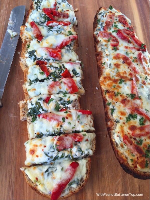 Spinach Dip Garlic Bread - made with multigrain bread, greek yogurt for creaminess, and topped with roasted red bell peppers. A sure crowd pleaser for taste - especially at 73 calories per slice!