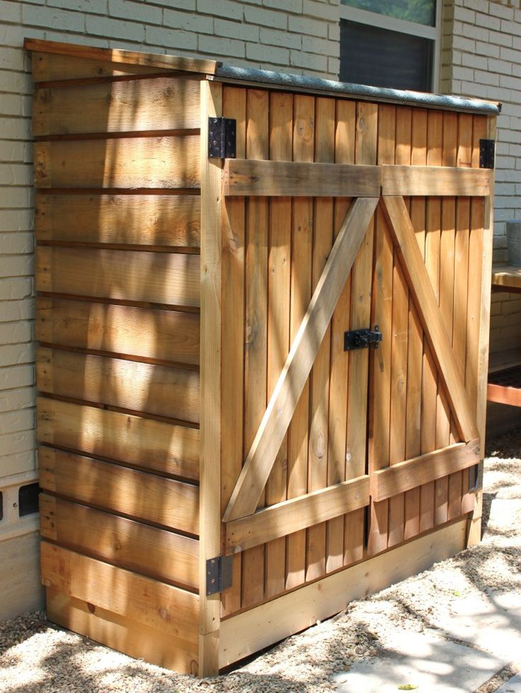 Storage Shed with Wood Slats on the Sides [5 feet wide, 5 feet high and 28 inches deep] hook & eye combo latch, 2 Ikea Bygel hang bars hanging small tools and hoses with S-hooks. storage bins and mounted hooks, built in shelves and corrugated roof.