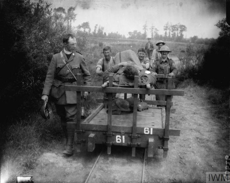 10 June 1917,  Battle of Messines, near Kemmel. Wounded man on a stretcher is taken to the rear on a trolley, by the side walks a military chaplain. ©IWM Q 5626