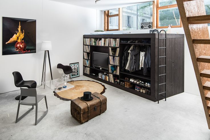 The Living Cube is a minimalist house located in Bern, Switzerland, designed by Till Könneker. The designer moved into a apartment studio without storage room so he made a minimalistic cube design with a shelf for his vinyl collection, a TV, and storage for clothes and shoes. A ladder on the side of the cube reveals a bed on top of the storage container. The entire piece is stained in black. (1)