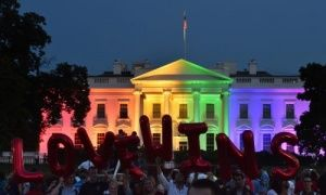 """People hold balloon letters reading """"Love wins"""" in front of the White House lit in rainbow colours in Washington on Friday night."""