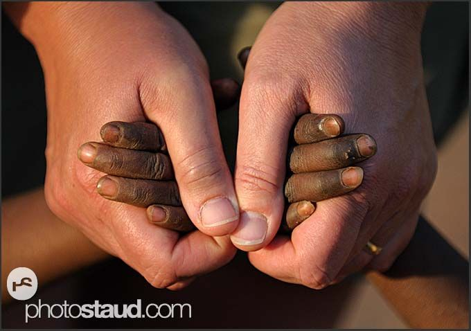 Hands in hands - tourist holding hands of African children, Zambia