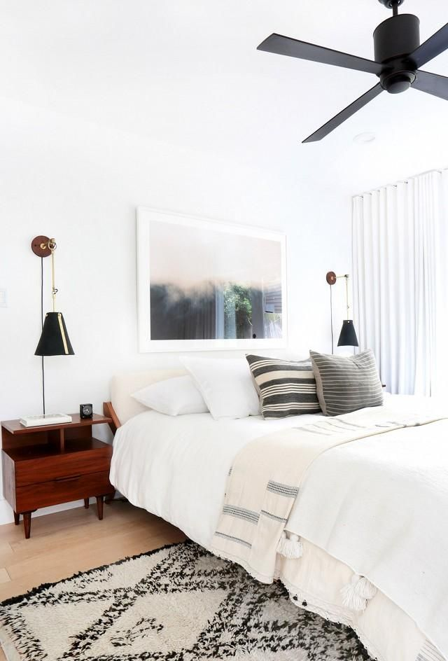Pops of rich wood contrast beautifully with crisp white and bold black accents in this fresh and modern, midcentury-styled master bedroom.