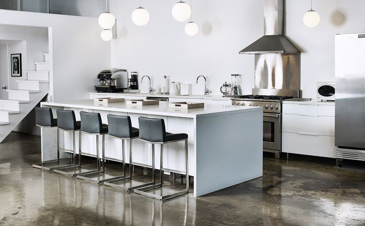 A custom shaped, white, concrete counter top in a modern kitchen of a studio. Sleek surfaces work well in a converted industrial studio. #Concrete #Kitchen #Studio #Interior #Design #Modern #Bar