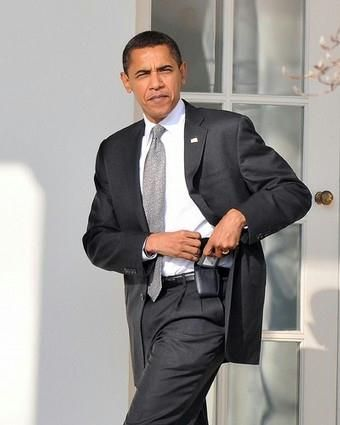 President Barack Obama places a Blackberry device back in the holster as he makes his way toward the Oval Office at the White House in Washington, January 29, 2009. Obama was allowed to keep the Blackberry after security modifications were made.